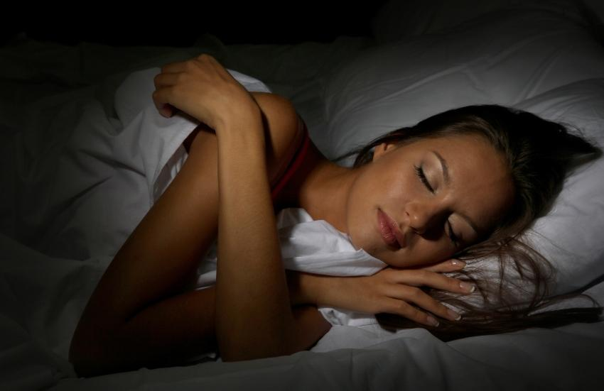 Junge Frau schläft tief und fest im Bett - heutige Schlafkultur