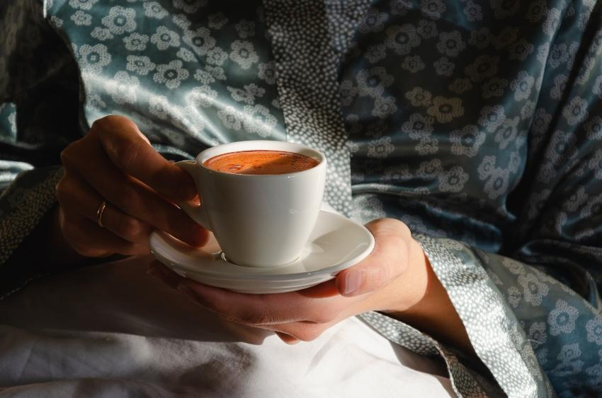 Frau trinkt Kaffee im Bett - Guten Schlaf fördern kann man so nicht