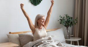 Frau wacht morgens glücklich auf - Immunsystem durch gesunden Schlaf stärken