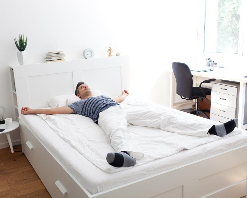 Junger Mann liegt im Bett