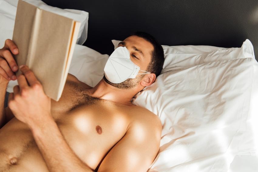 Mann mit Mund-Nase-Schutz liegt im Bett und liest