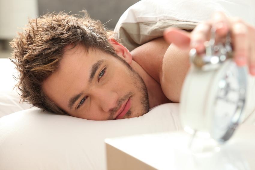 Mann schaltet morgens den Wecker aus - Schlafrestriktion basiert auf bewusstem Verzicht von langen Bettzeiten