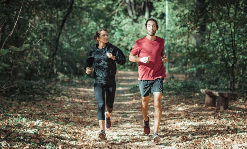 Junges Paar joggt im Wald - für das Konzept der Schlafrestriktion ist körperliche Auslastung wichtig