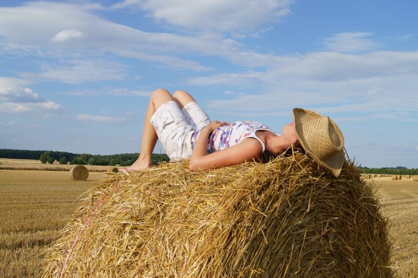 Frau schläft auf Strohballen