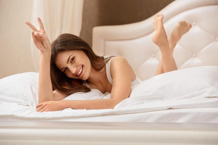 Junge Frau liegt glücklich im Bett