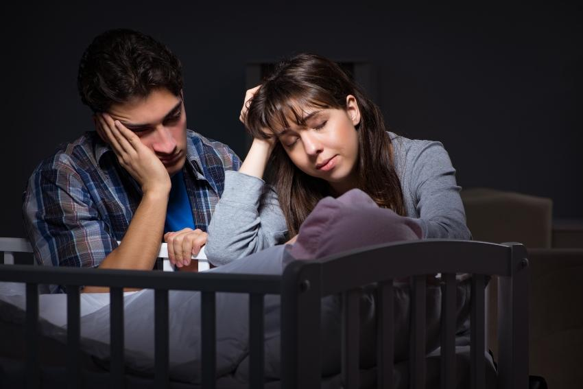 Eltern übermüdet am Kinderbett - Ammenschlaf bedeutet unregelmäßig Schlafen