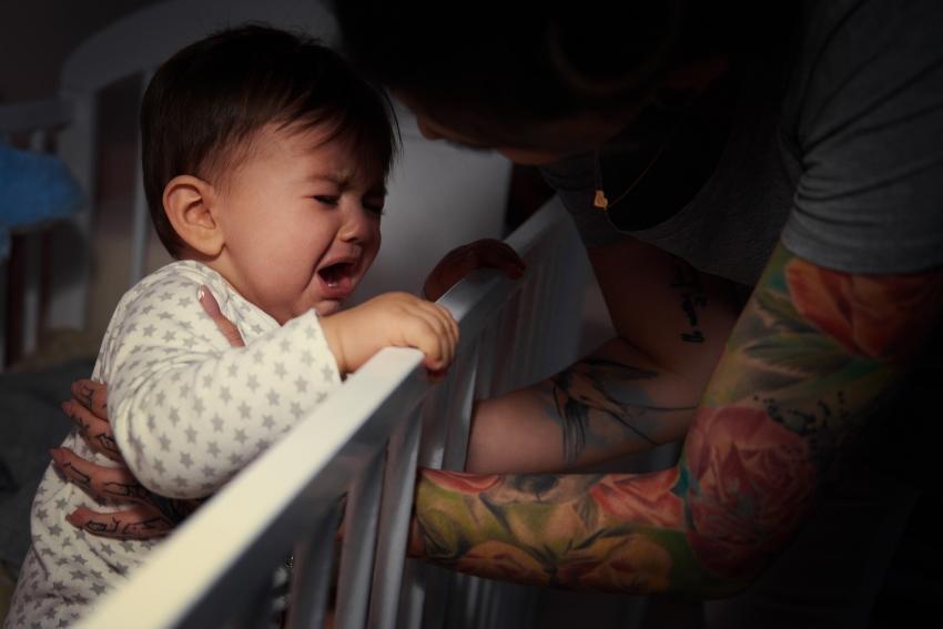 Baby wird von Mutter im Kinderbett beruhigt - Ammenschlaf der Eltern
