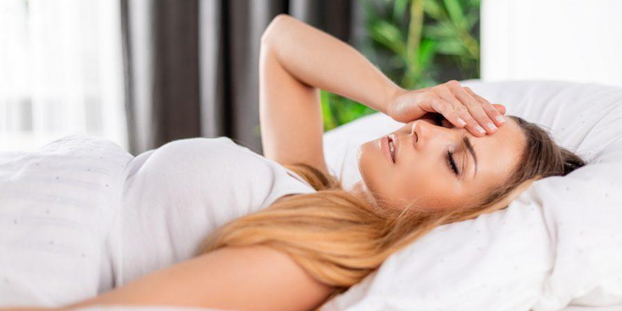 Junge Frau im Bett mit Kopfschmerzen - Morgens mit Kopfschmerzen aufwachen