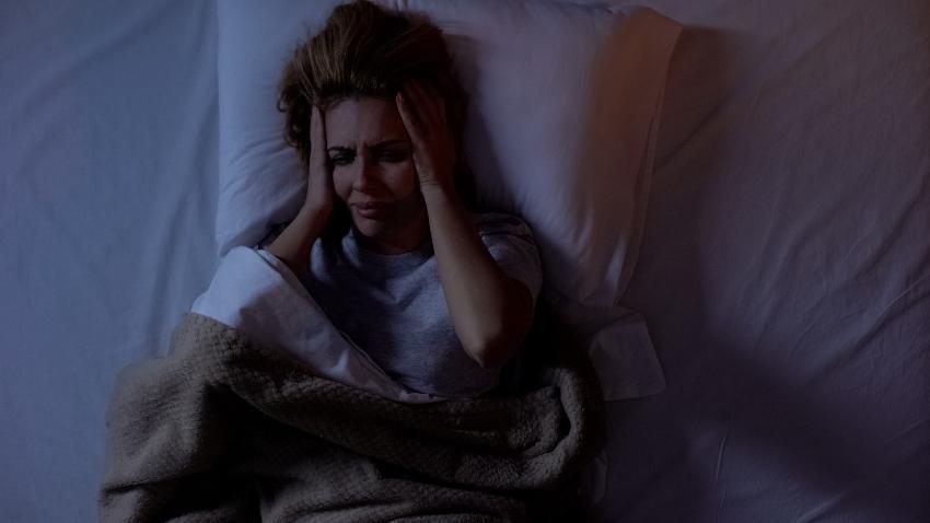 Frau mit Kopfschmerzen im Bett
