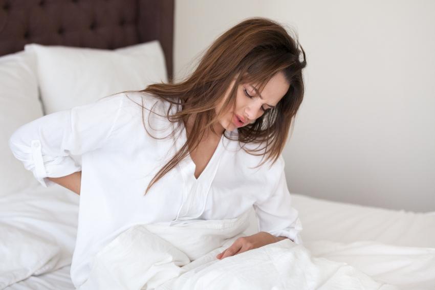 Junge Frau im Bett hält sich den Rücken vor Schmerzen