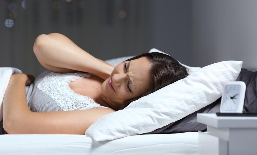 Mann liegt im Bett und fasst sich in den Nacken - Morgens mit Kopfschmerzen aufwachen