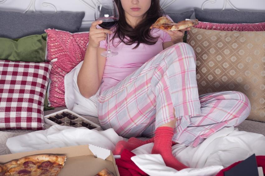 Junge Frau mit Weinglas und Pizza im Bett