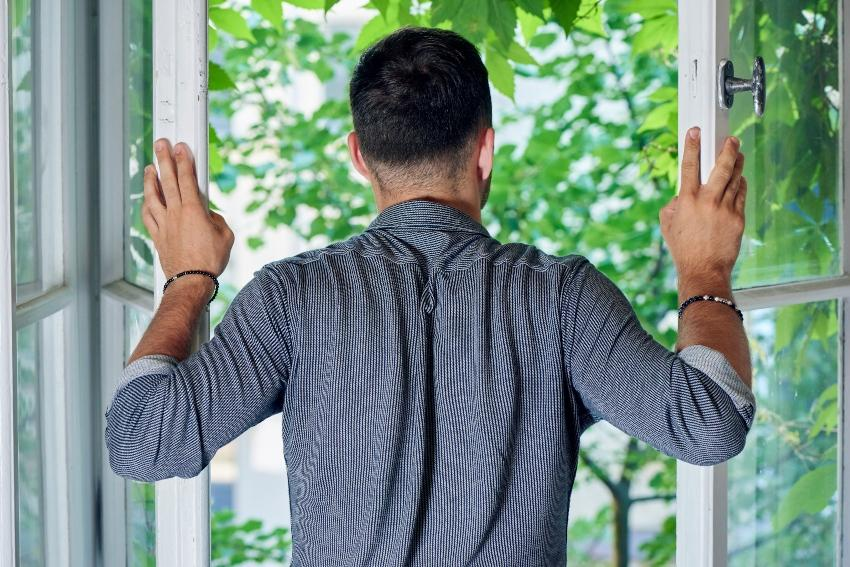 Mann steht am geöffneten Fenster