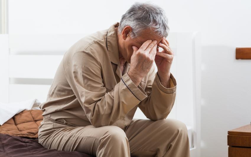 Mann sitzt im Bett mit Kopfschmerzen - Morgens mit Kopfschmerzen aufwachen