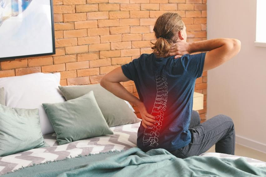 Junger Mann sitzt im Bett mit Rückenschmerzen - Rückenschonende Matratzen können helfen