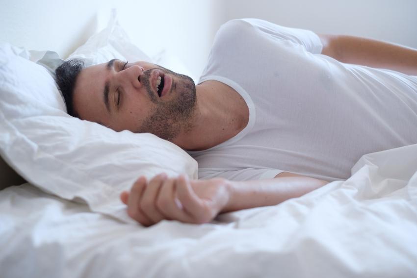 Mann schläft mit offenem Mund - Morgens mit Kopfschmerzen aufwachen durch Schlaf-Apnoe