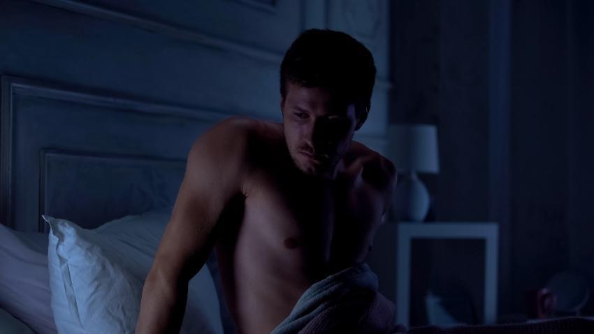 Junger Mann wacht im Bett auf - Schichtarbeit als Auslöser von Schlafproblemen