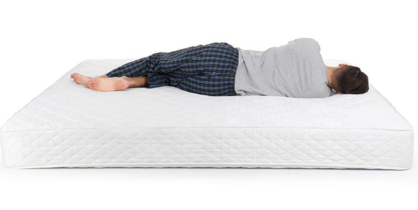 Mann liegt im Bett - Rückenschonende Matratzen