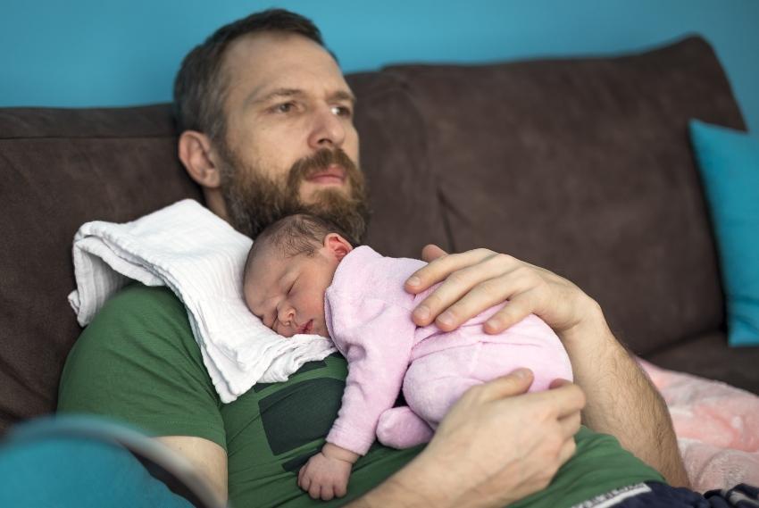 Vater hat schlafendes Baby auf dem Arm