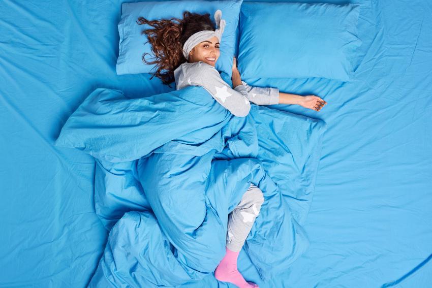 Mit Socken schlafen : Junge Frau im Bett mit Socken