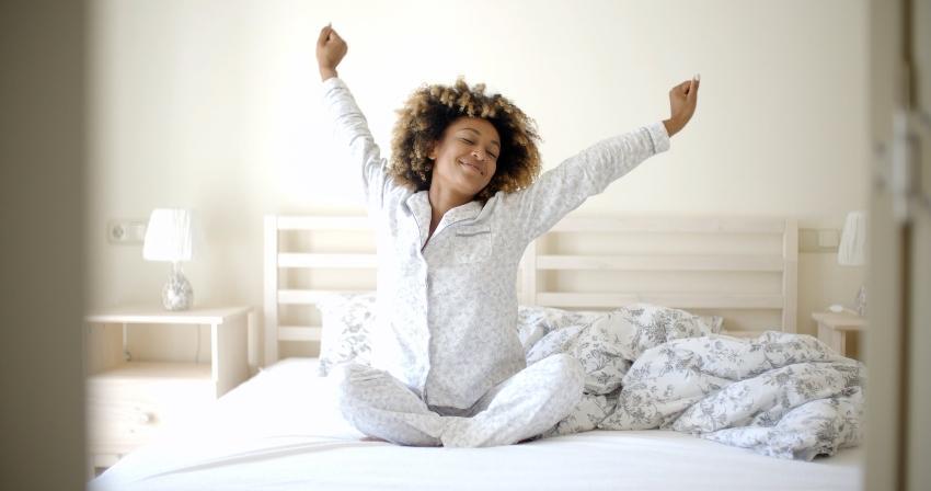 Junge Frau wacht fröhlich im Bett auf