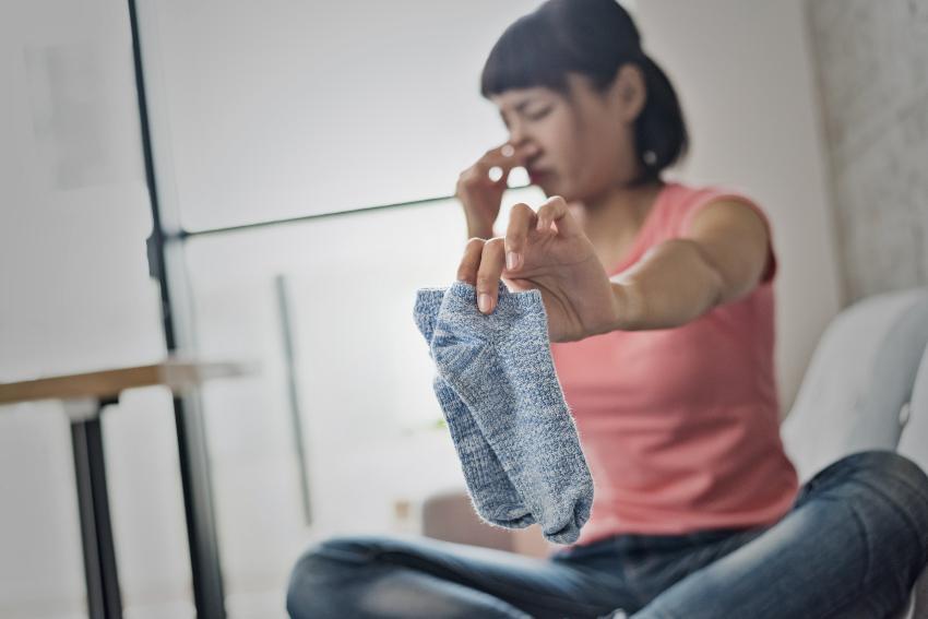 Junge Frau hält sich die Nase zu - mit Socken schlafen kann stinkende Socken zur Folge haben