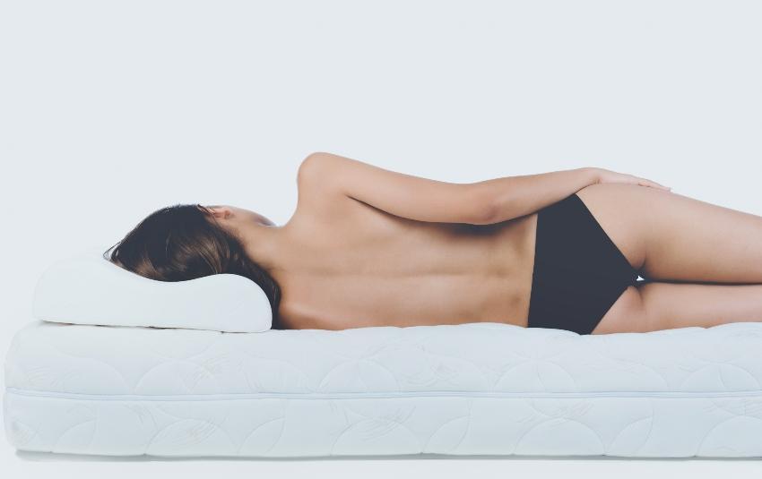 Junge Frau liegt seitlich im Bett - Druckentlastung bei Matratzen sorgt für gerade Wirbelsäule