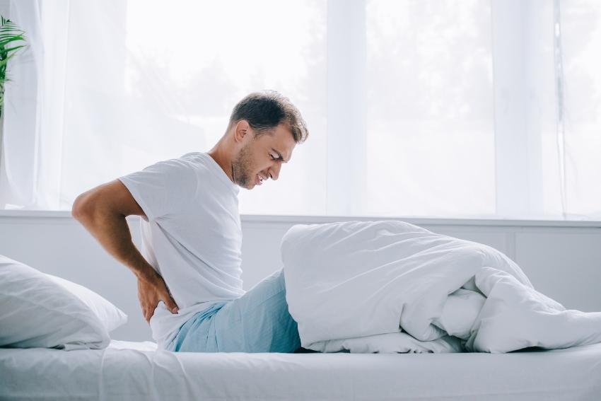 Mann mit Rückenschmerzen im Bett - Druckentlastung bei Matratzen ist wichtig