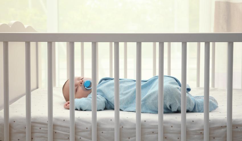Baby liegt rücklings in Babybett - Sicherer Babyschlaf