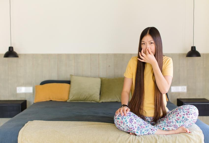 Junge Frau sitzt im Bett und hält sich die Nase zu