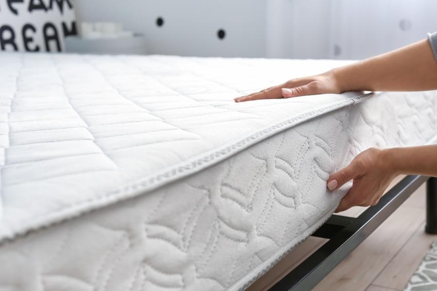 Jemand prüft die Matratze im Bett - Matratzenvergleich beim Neukauf ist wichtig
