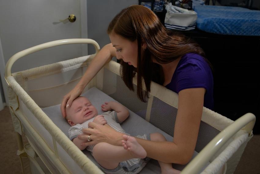 Mutter prüft die Temperatur ihres Babys - Sicherer Babyschlaf kann gefördert werden
