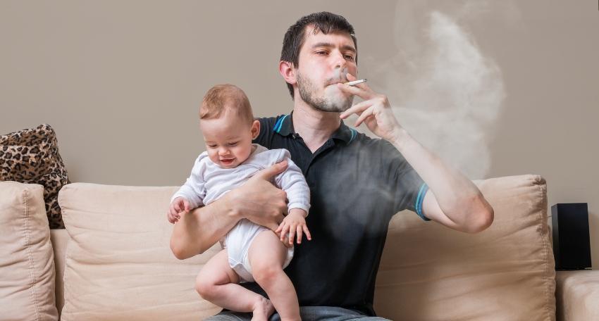 Junger Mann rauch mit Baby mit Arm