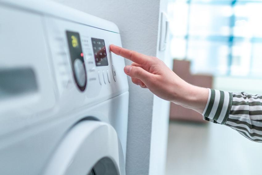 Frau stellt Waschmaschine ein - Bettwanzen bekämpfen durch hohe Waschtemperatur