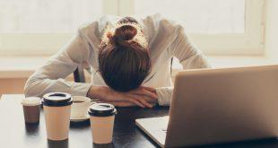 Junge Frau schläft am Schreibtisch - Übermüdung im Beruf
