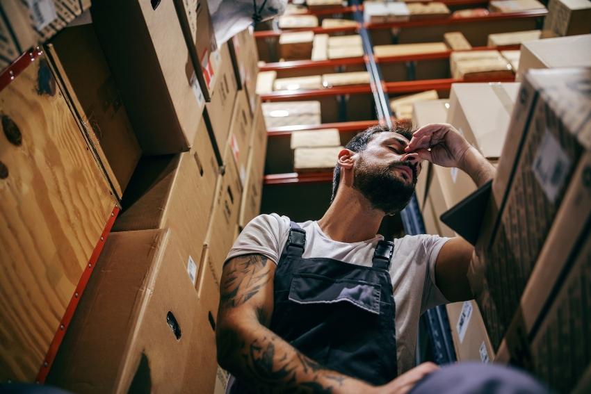 Junger Arbeiter übermüdet in einem Lager mit Kartons - Übermüdung und Erschöpfung