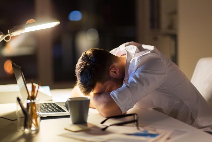 Junger Mann schläft am Schreibtisch