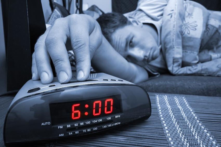 Junger Mann greift morgens um 6 zum Wecker