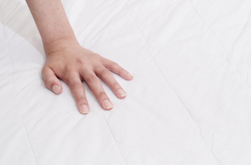Hand drückt auf Matratze