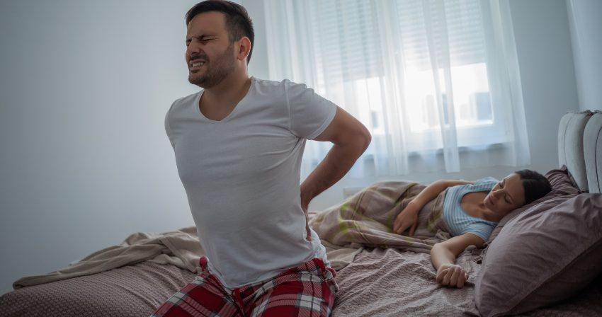 Mann im Bett mit Rückenschmerze - vielleicht hilft ein Matratzentausch