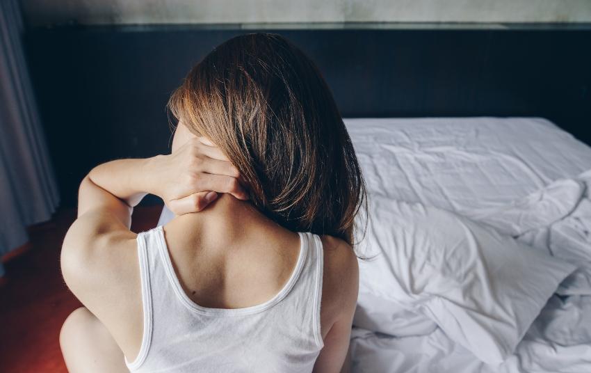 Junge Frau im Bett fasst sich an den schmerzenden Nacken - Matratzentausch als mögliche Lösung