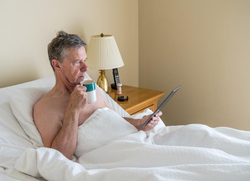Älterer Herr sitzt lesend im Bett mit Motorlattenrost