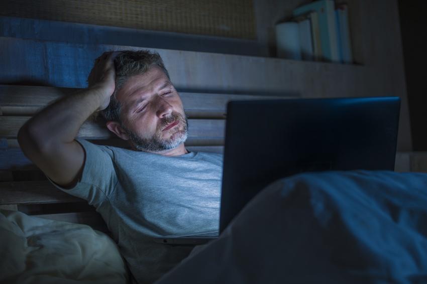 Junger Mann ermüdet, spät abends im Bett liegend mit Laptop - Home Office im Bett