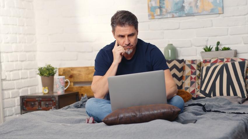 Junger Mann mit Laptop - Home Office im Bett