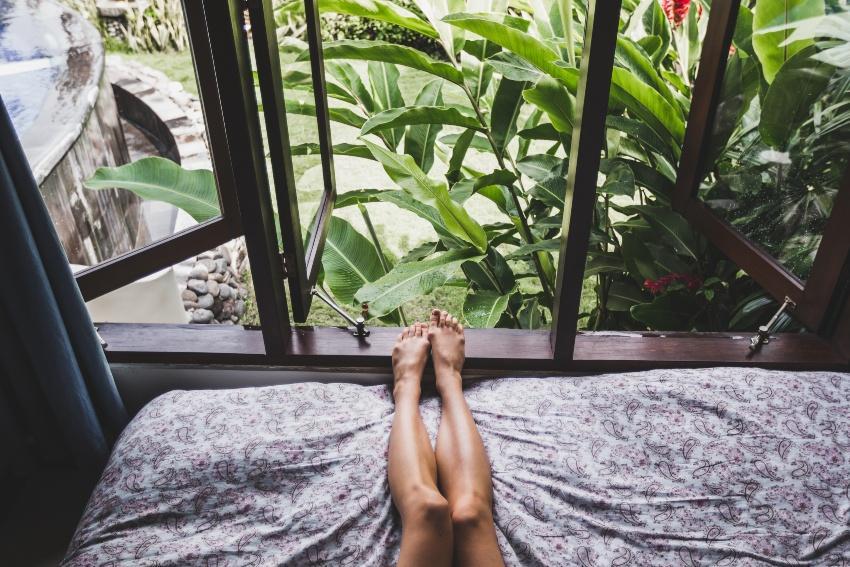 Frau liegt mit den Beinen in Richtung geöffnetem Fenster - Schlafzimmer zu warm