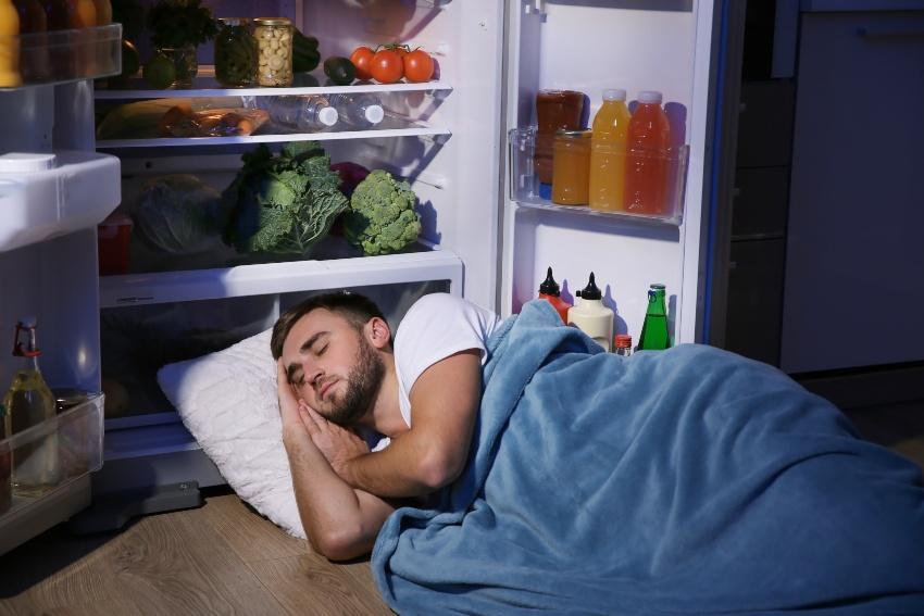 Junger Mann schläft neben geöffnetem Kühlschrank - Schlafzimmer zu warm