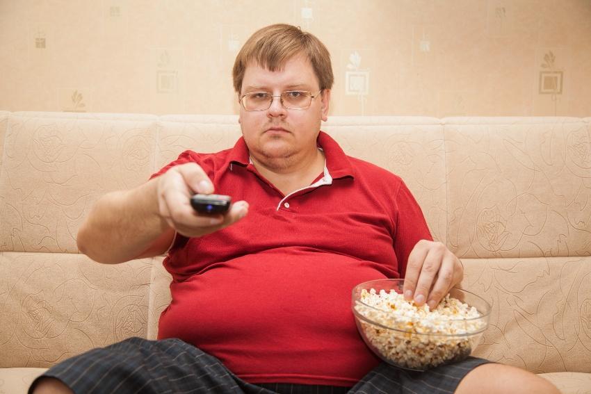Mann mit deutlichem Übergewicht sitzt mit Popcorn vorm Fernseher - Diabetes Schlafstörungen