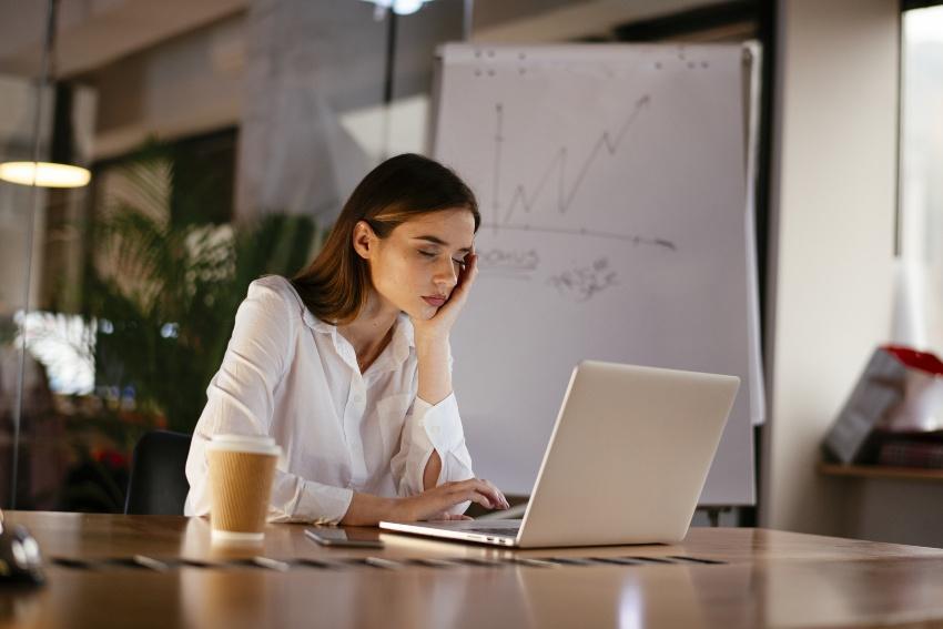 Junge Frau schlafend im Sitzen im Büro am Laptop - Diabetes Schlafstörungen