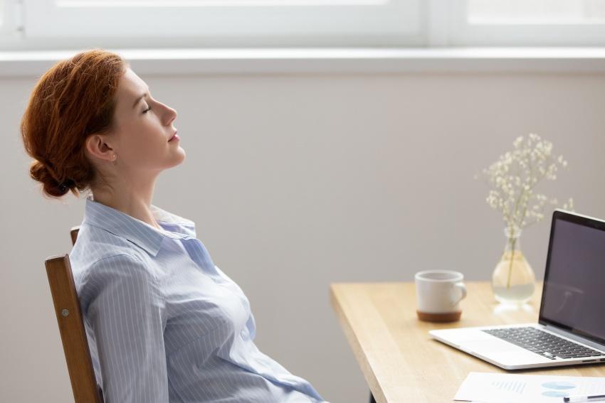 Junge Frau schläft im Sitzen am Arbeitsplatz