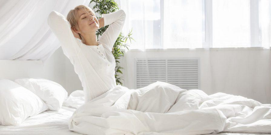 Junge Frau wacht auf - Antibakterielle Bettwäsche